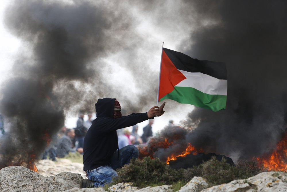 A protester holds a Palestinian flag as smoke rises from burning tires during clashes with Israeli security forces near the West Bank city of Ramallah last week.