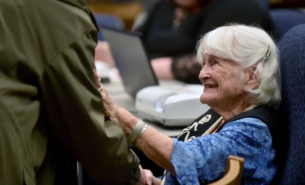 Hope Wing Weston, daughter of Eugene Wing, greets history buffs Wednesday before a presentation about her father at the Lawrence Junior High School library in Fairfield.
