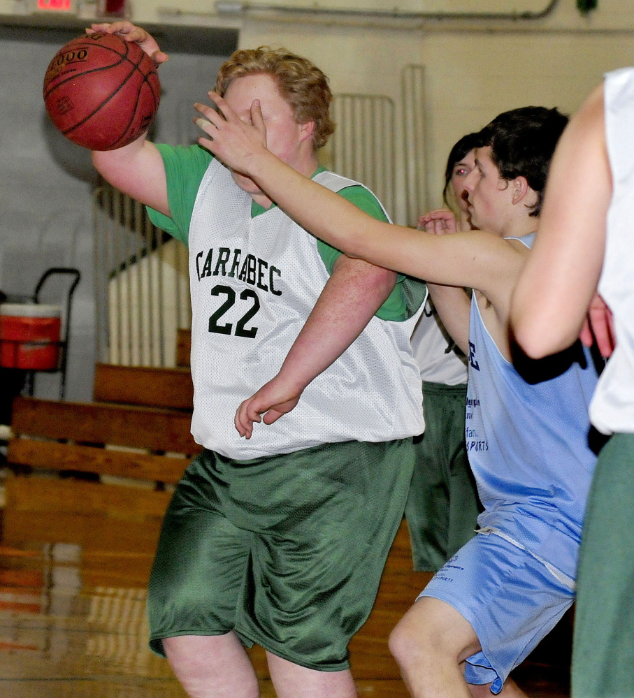 Carrabec's Dalton Way tries to get past an Oceanside defender during a unified basketball North quarterfinal Wednesday afternoon in North Anson.