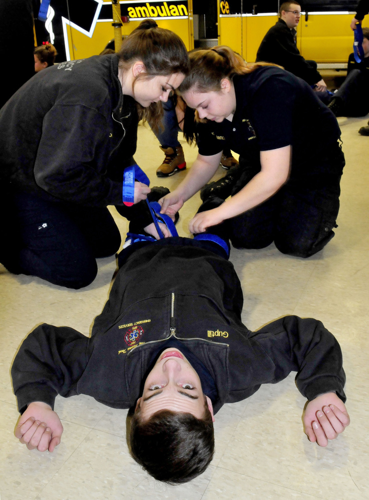 Mid-Maine Technical Center students apply tourniquets to Hunter Guptill on Thursday during training by Homeland Security expert Paul Brooks on stopping bleeding at the school in Waterville. The students are Ashley Leighton, left, and Emily Melancon.