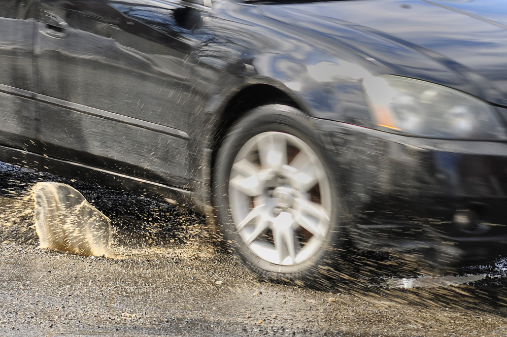 A car splashes through a pothole Wednesday at the corner of Water and Bridge streets in Gardiner.