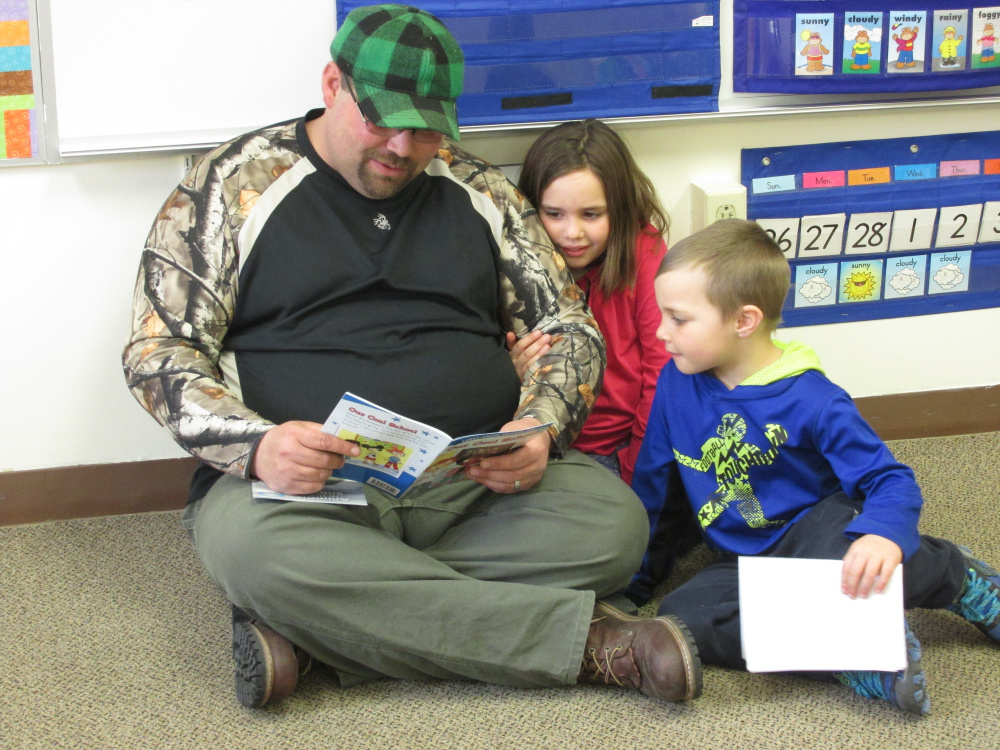 Eugene Worster read with his children, Remington and Melynda, during Dr. Seuss Day on March 2 at Forest Hill Elementary School in Jackman.