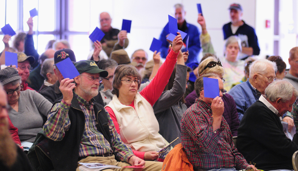 """Residents hold up blue cards to vote """"yes"""" on a warrant item Saturday during the China Town Meeting in the China Middle School gymnasium."""