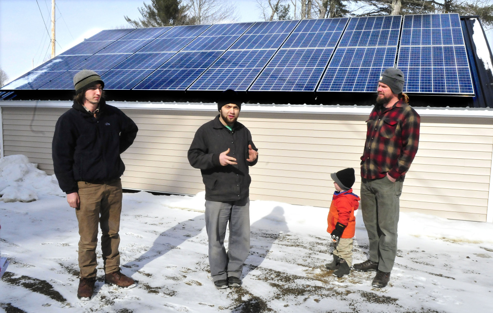 Joas Hochstetler, center, manager at Backyard Buildings in Unity, talks about the shed built at the Unity shop on Wednesday. At right is Matt Wagner, project manager for Insource Renewables, and his son, Ansel. Insource employee Ben Holt is at left.