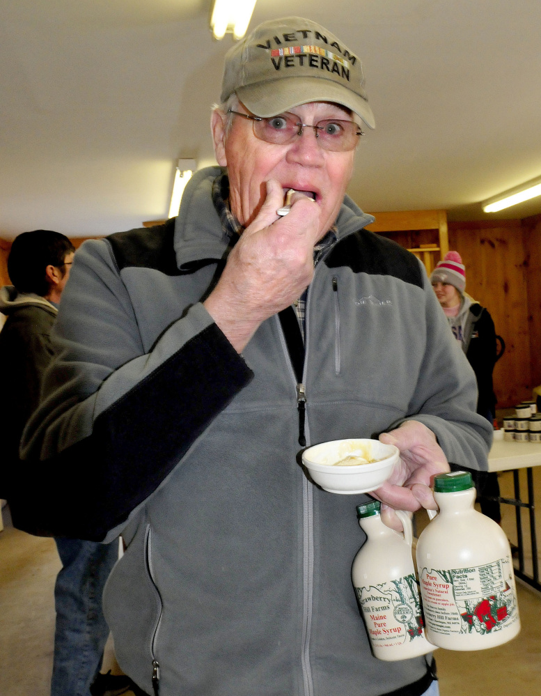"Holding two quarts of fresh maple syrup, Alfred Labonte samples syrup poured over ice cream at Strawberry Hill Farm in Skowhegan on Maine Maple Sunday. ""I have to do this event every year,"" Labonte said."