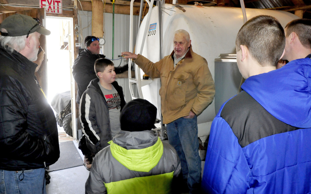 As Jeremy Steeves, background, fills tanks with maple sap, his father, Jack Steeves, conducts a tour of the sugarhouse at Strawberry Hill Farm in Skowhegan on Maine Maple Sunday.