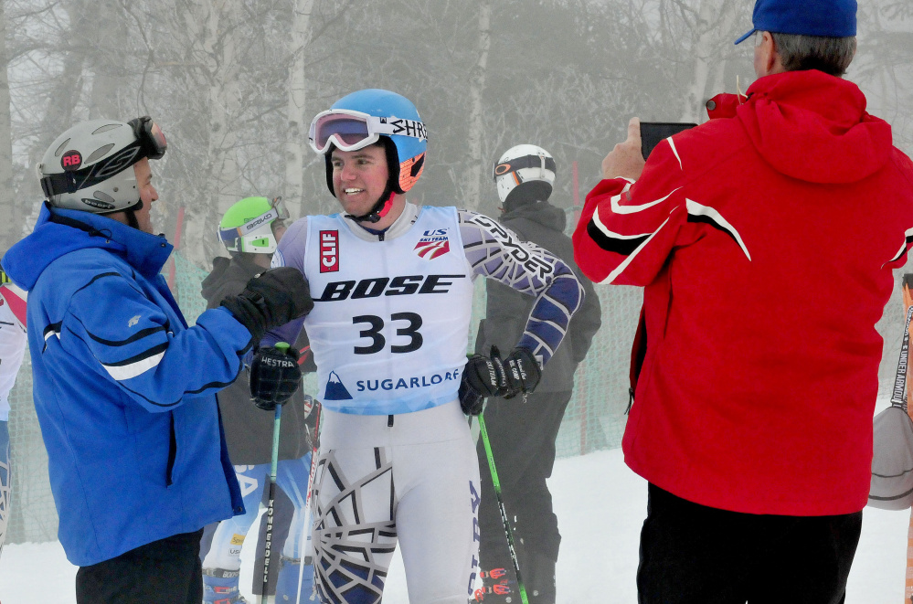 Colby student Michael Boardman talks with his father Jeff, left, after competing in a giant slalom race at the U.S. Alpine Championships on Tuesday at Sugarloaf Mountain. At right Bob Haskell, father of competitor Mardi Haskell, photographs the Boardmans.