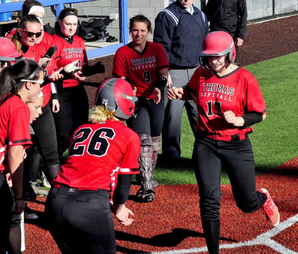 Thomas' Korrie Laren touches home plate as teammates congratulate her after she hit a home run against Coby on Thursday in Waterville. The run was the only one scored in the game as the Terriers won 1-0.