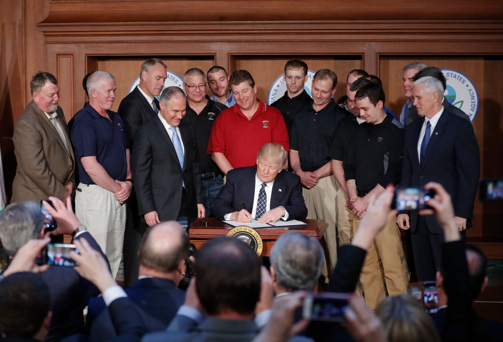 President Trump, accompanied by EPA Administrator Scott Pruitt, third from left, and Vice President Mike Pence, right, signs an executive order on Tuesday at the EPA headquarters in Washington.