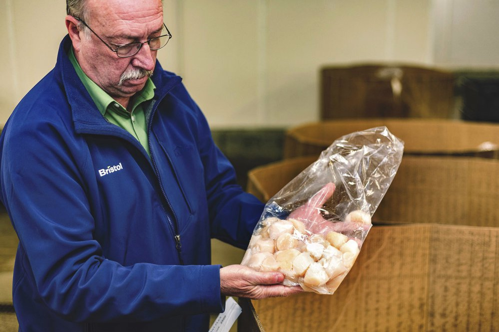 Rick Elliott of Bristol Seafood in Portland examines a bag of scallops at auction in New Bedford, Mass. Fair trade certification status is now gaining prominence with seafood in the U.S., where interest is growing in the story behind the fish and shellfish people consume.
