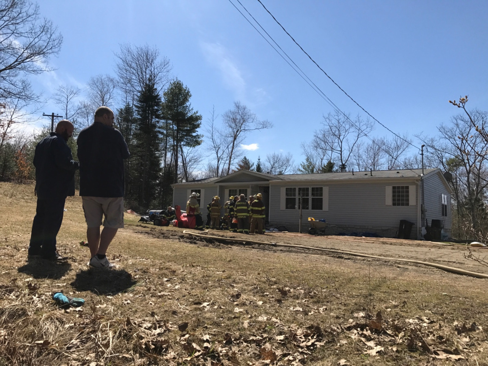 Enos Webster Jr., right, stands outside his mobile home at 1351 South Clary Road after a fire started in his bathroom Monday afternoon. Webster tried to put the fire out himself, but soon had to call firefighters to the scene.