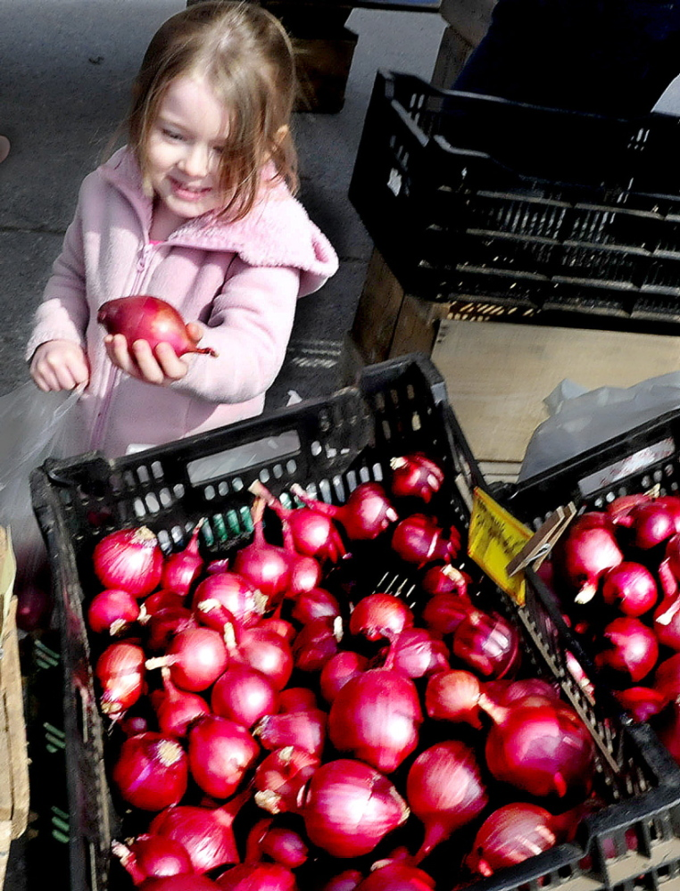 Jacklynn Lee, of Fairfield, seems pleased with her selection of red onions from Snakeroot Organic Farm on the first day of the Downtown Waterville Farmers' Market on The Concourse on April 17, 2014. The farmers market has to move this year to make way for Colby's student residence. The council will vote on whether to close Common Street to create space for the Thursday farmers market's 2017 outdoor season.