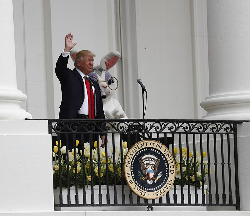 President Trump accompanied by the Eastern bunny, waves from the Truman Balcony of the White House.