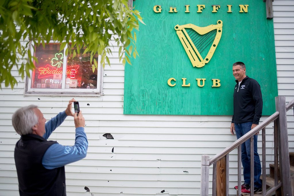 Rick Wilson takes a photo of Charlie Gordon in from of the Griffin Club sign before going in Wednesday evening. Gordon played on one of Eddie Griffin's basketball teams when he was young. He and Wilson, who had never been to the bar, drove down from Brunswick for one last drink.