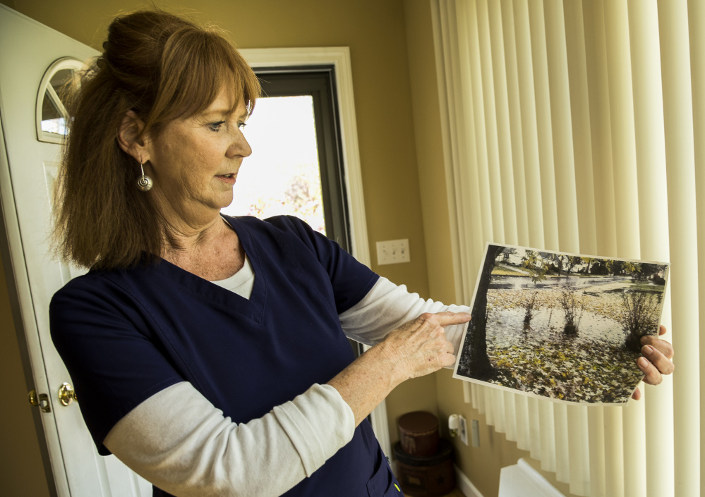 Jacquelyn Cyr of Windsor Avenue in Augusta on Wednesday holds a photo she took of standing water in her yard.
