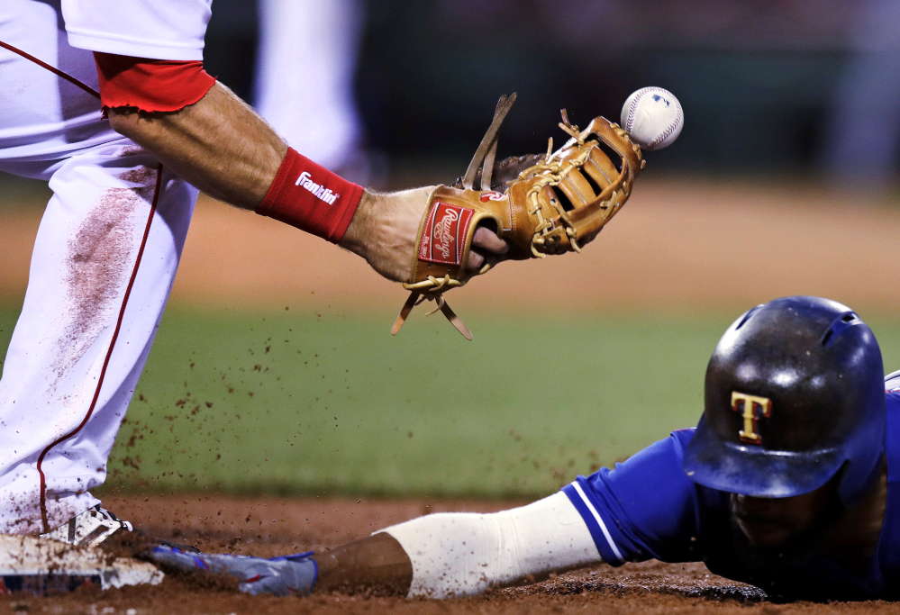 The ball bounces away from Boston Red Sox first baseman Mitch Moreland, left, while trying to unsuccessfully make a pick-off tag on Texas runner Delino DeShields during the fifth inning Tuesday.