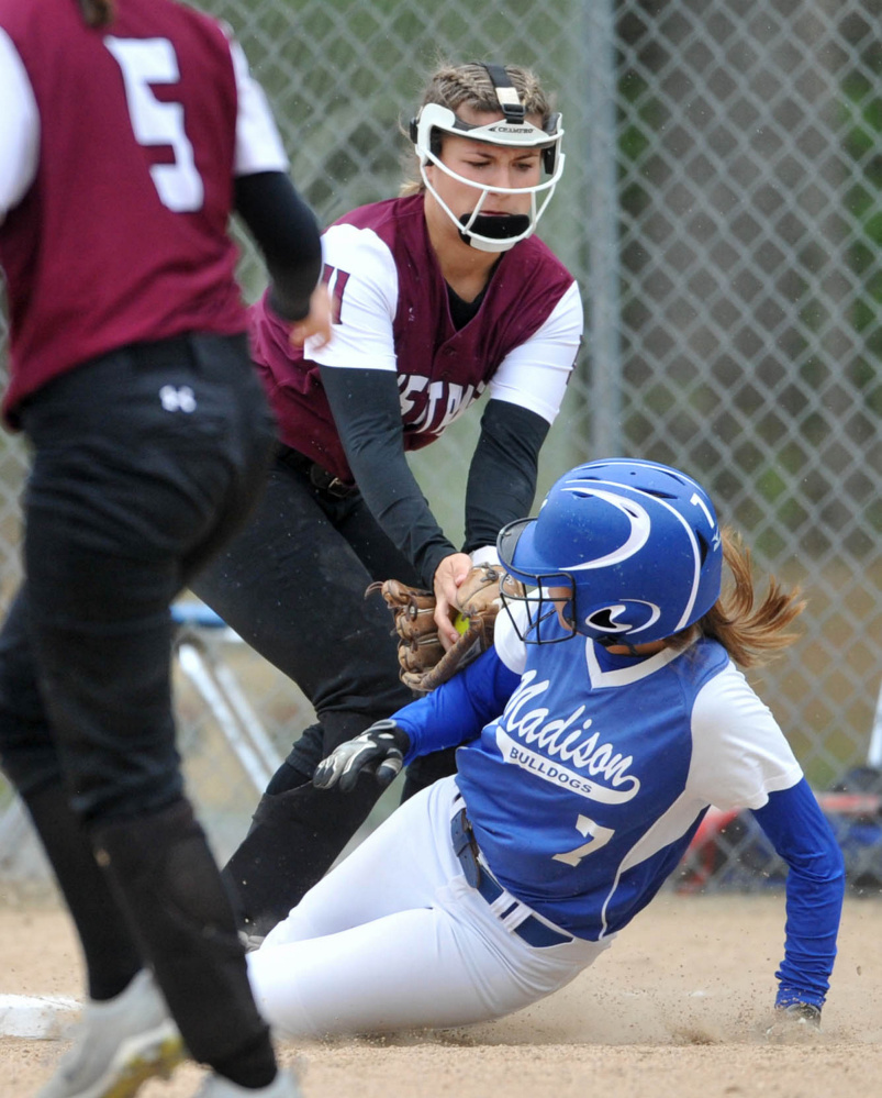 Madison Area Memorial High School's Sydney LeBlanc (7) slides safely into third base under the tag from Monmouth Academy's Hannah Anderson (11) in Madison on Thursday.