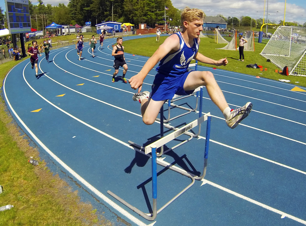 Erskine's Elliot Stinchfield runs the 300 meter hurdles at the Kennebec Valley Athletic Conference track and field championships Saturday at McMann Field in Bath.