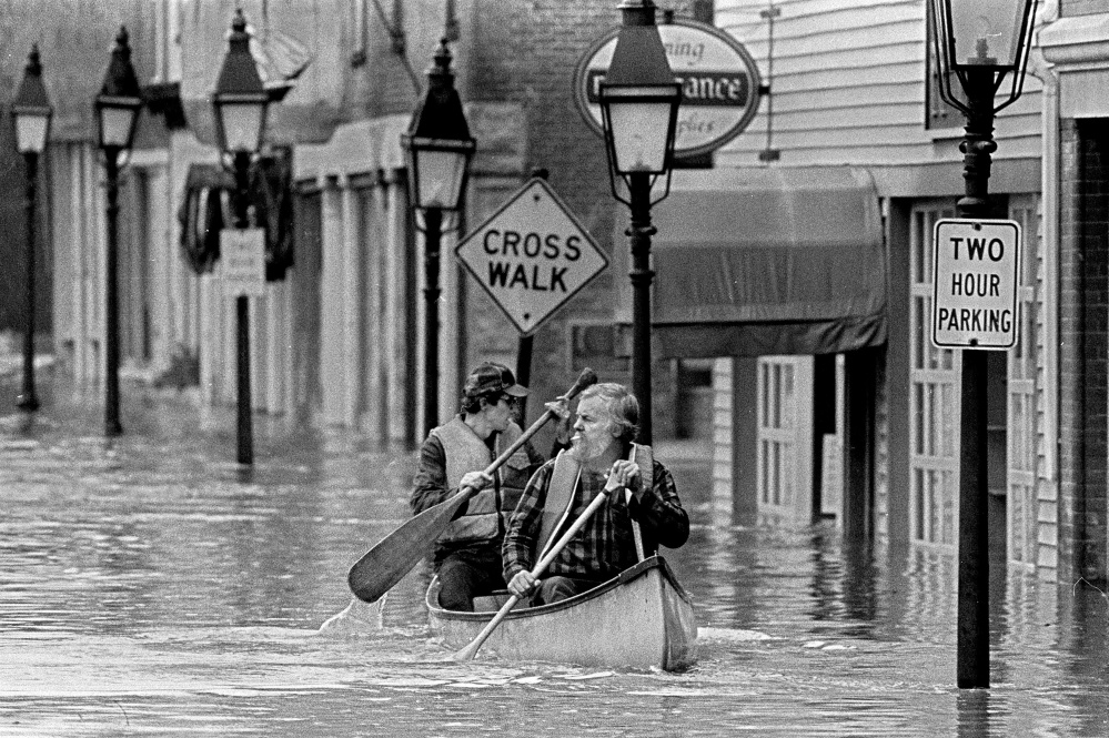 "This April 1987 file photo Sumner ""Sam"" Webber, left, and John Jacques paddling a canoe on Water Street just past Central Street after the Kennebec River flooded downtown Hallowell."