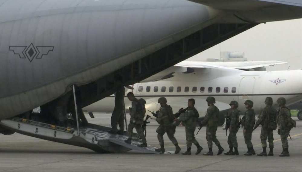 In this image made from video, marines board a transport plane in Manila, Philippines. A marine battalion left an air force base in Manila on deployment to the southern city of Marawi where ongoing violence has killed scores of people.