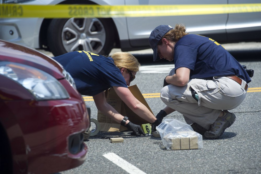 FBI Evidence Response Team members mark evidence at the scene of Wednesday's shooting in Alexandria, Va., in which House Majority Whip Steve Scalise of Louisiana and four others were shot during a congressional baseball practice.