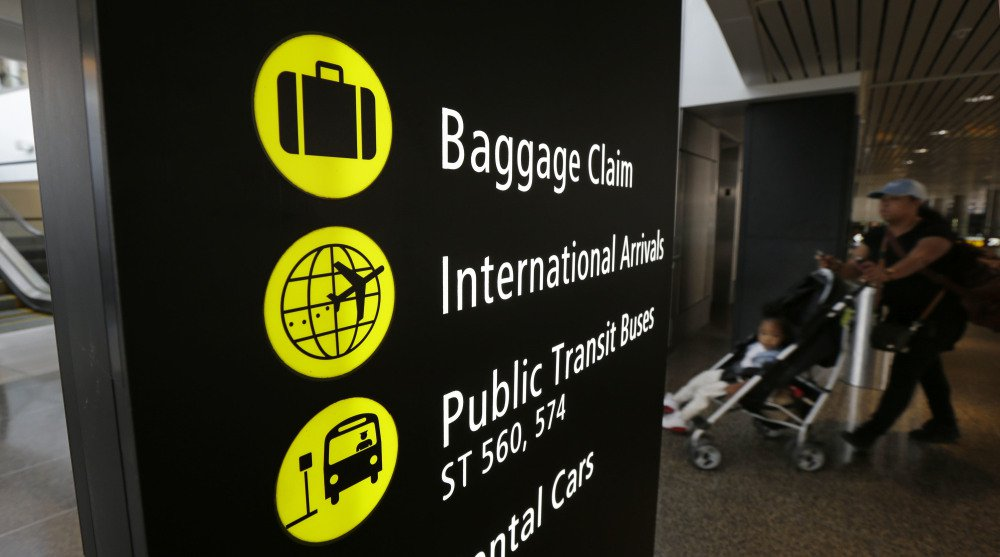 """A woman pushes a stroller near a sign for international arrivals Monday at the Seattle-Tacoma International Airport. The U.S. Supreme Court said Monday that President Trump's travel ban on visitors from Iran, Libya, Somalia, Sudan, Syria and Yemen can be enforced if those visitors lack a """"credible claim of a bona fide relationship with a person or entity in the United States."""""""