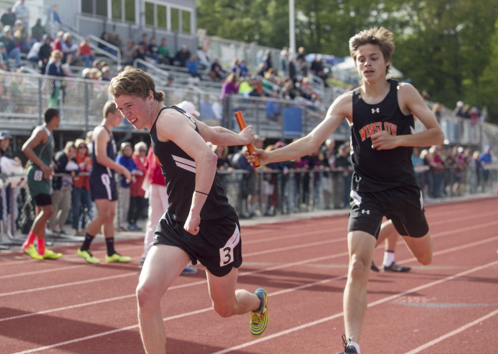 Winslow senior Spencer Miranda hands off the baton to Ben Smith during the 4x400 relay race at the Class B track and field state championship meet Saturday in Yarmouth.