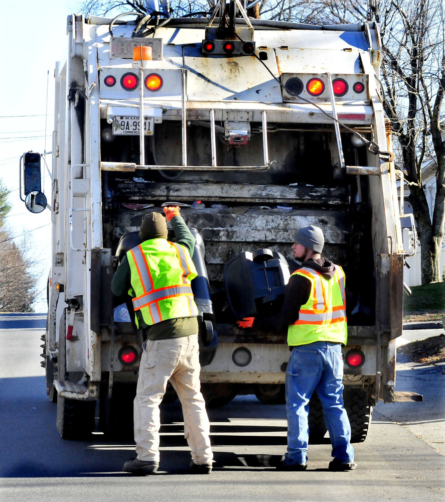 Winslow Public Works employees Josh Whitman, left, and Jacob Solomon fill a trash truck on Nov. 30, 2015. The Winslow Town Council has approved a pilot program that reportedly might divert 10 to 15 percent more of the town's waste from trash to recycling.