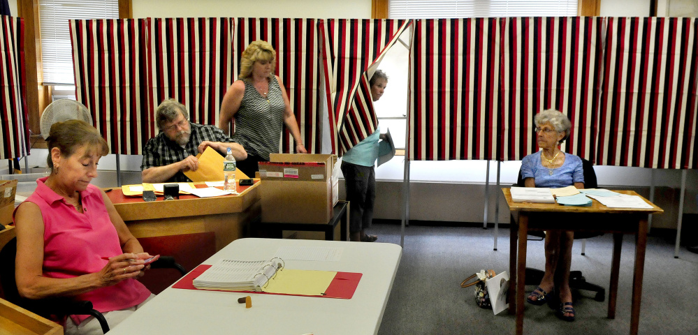 Ballot clerks outnumbered voters, including Sydney Dunbar, exiting the voting booth, by a 4-to-1 ratio in this photograph taken Tuesday during voting in Skowhegan. Clerk Linda Smith, left, said turnout was light as she worked on a word game on her cellphone.