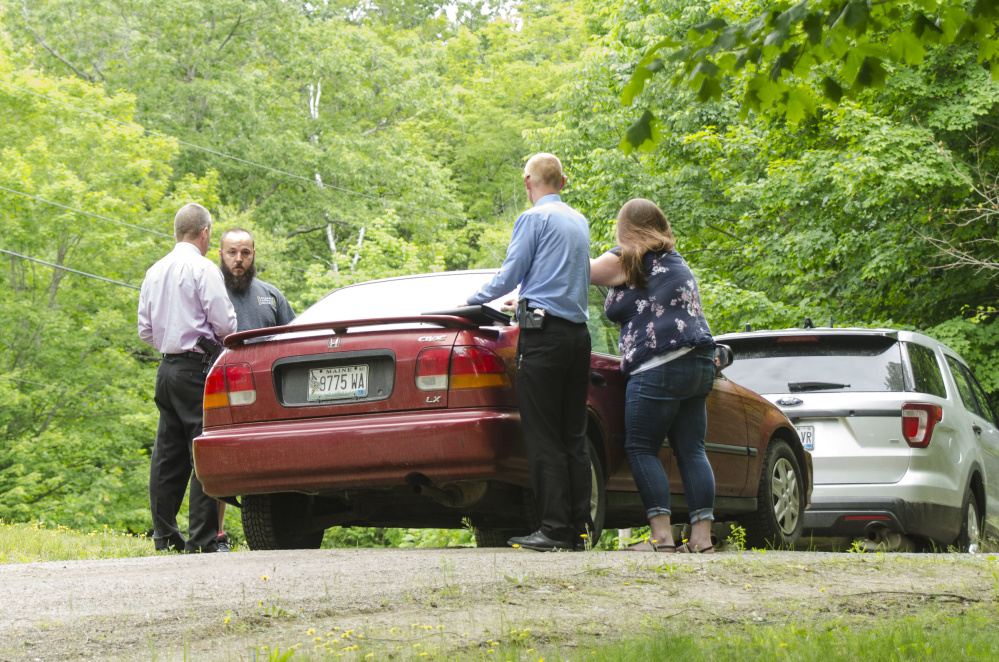 Sgt. Christopher Tremblay, left, and Detective Benjamin Sweeney, second from right, both of the Maine State Police, talk on Saturday afternoon on Yeaton Drive in West Gardiner with relatives of a man who was shot to death there early that morning. The victim, James Haskell, 41, was a visitor at the property, according to Steve McCausland, spokesman for the Maine Department of Public Safety.