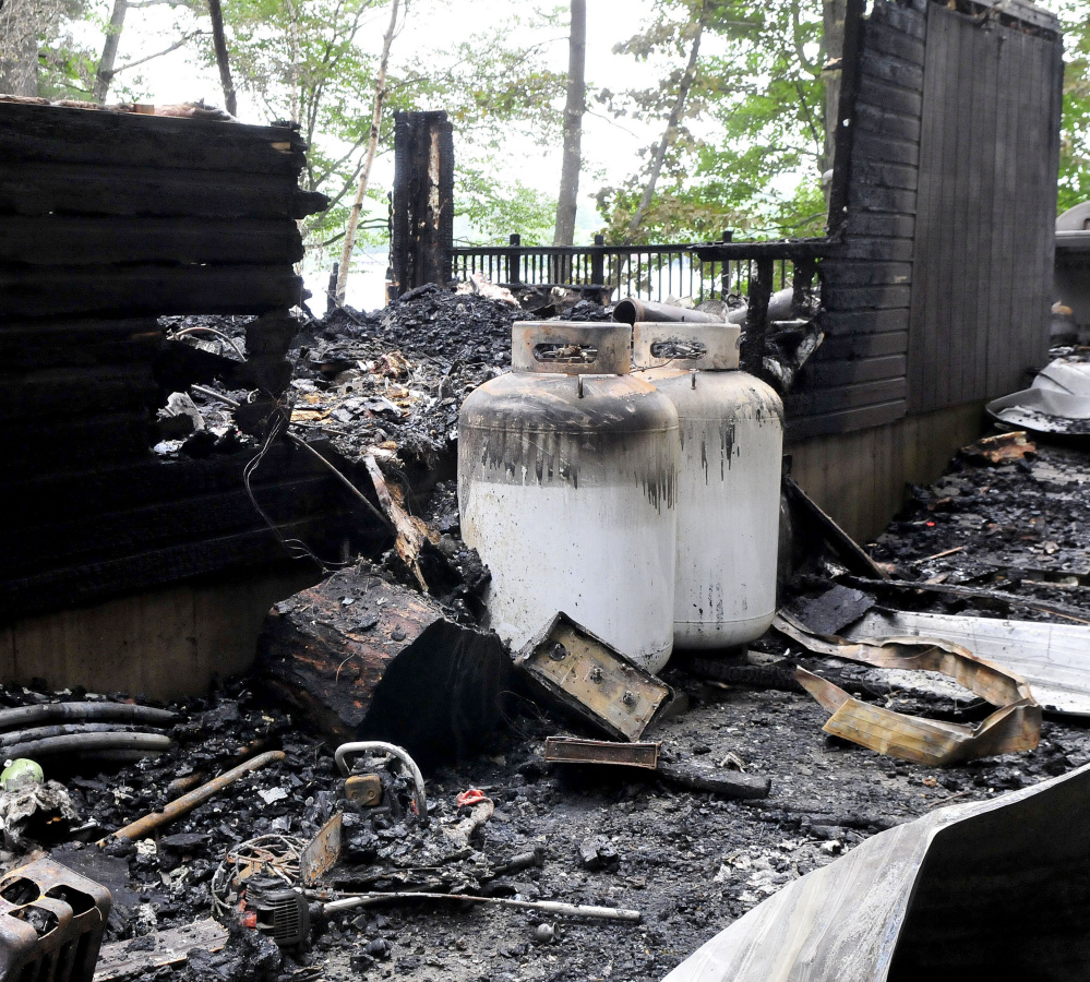 Two large propane tanks were scorched but did not explode at this cottage on Brickett Point Road on East Pond in Oakland. The home was destroyed by fire on Saturday.