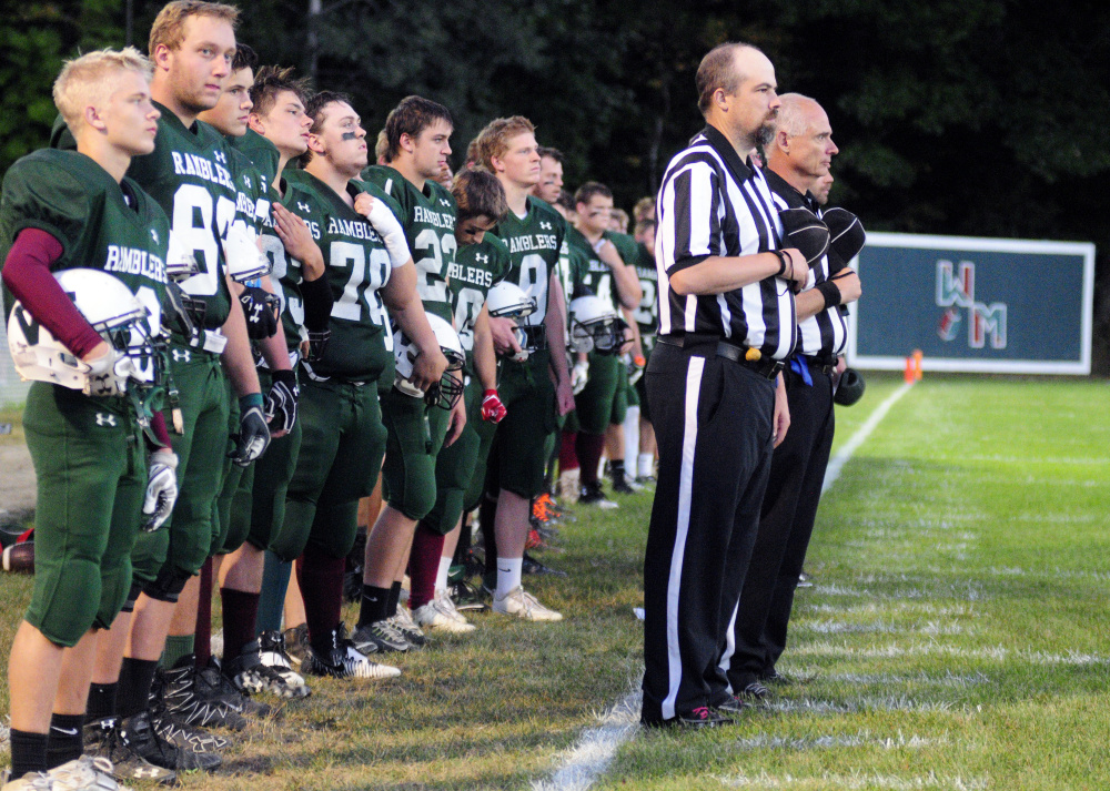 Members of the Winthop/Monmouth football team and officials stand during the national anthem prior to a Campbell Conference Class D game against Dirigo last season in Winthrop. There is growing momentum to add Hall-Dale to the co-op.
