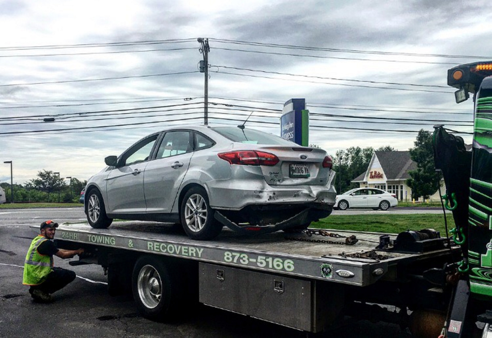 A tow truck removes one of two cars involved in a rear-end crash Saturday morning on upper Main Street in Waterville that, according to police, injured both drivers slightly.