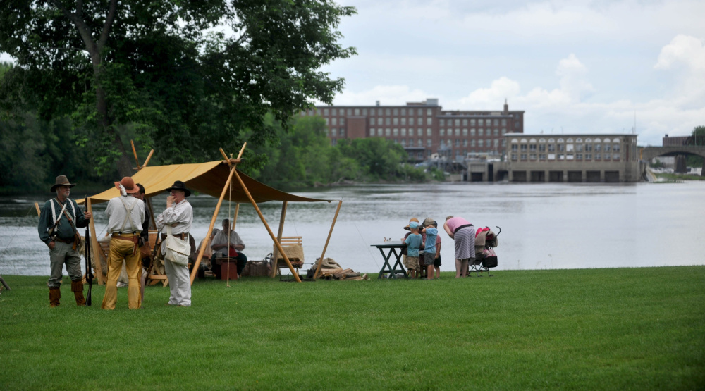 Re-enactors stand at their camp Saturday along the east bank of the Kennebec River with Waterville's Hathaway Creative Center in the background at the annual Fort Halifax Days at Fort Halifax Park in Winslow.