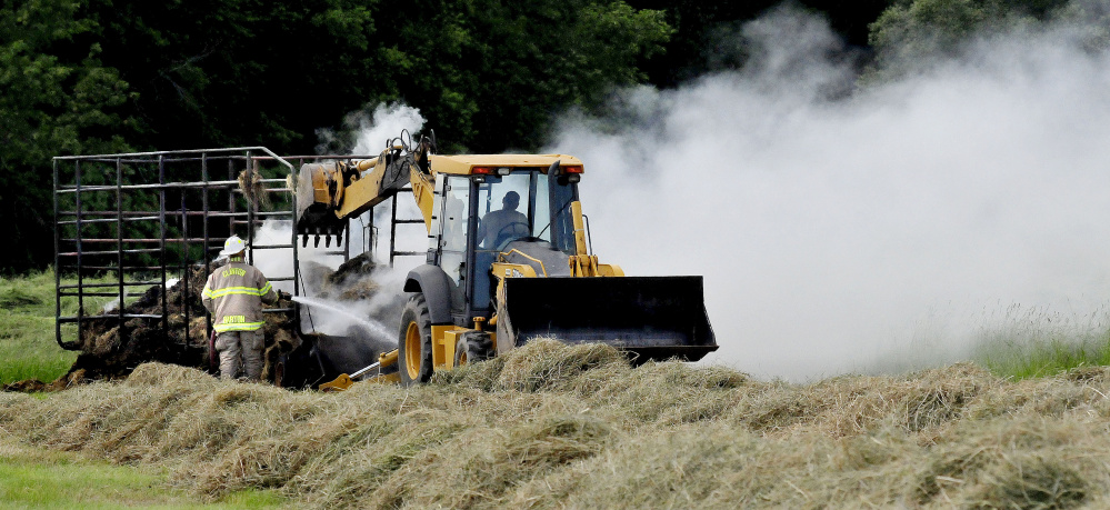 As a Clinton firefighter spays water on smoldering hay a bucket loader operator prepares to knock the hay off a wagon that was destroyed by fire in a field off Gogan Road in Clinton on Sunday.