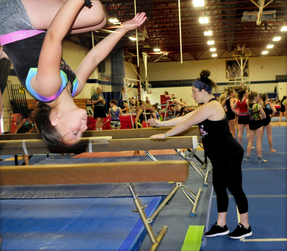 An area gymnast flips on a beam as Olympic gold medalist Carly Patterson watches other young gymnasts train Thursday at the Alfond Youth Center in Waterville.