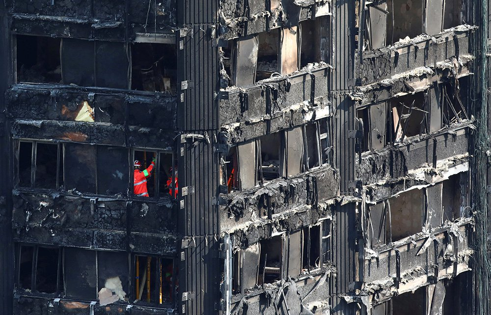 Investigators work inside  the burned-out remains of the Grenfell apartment tower in North Kensington, London, on Sunday.