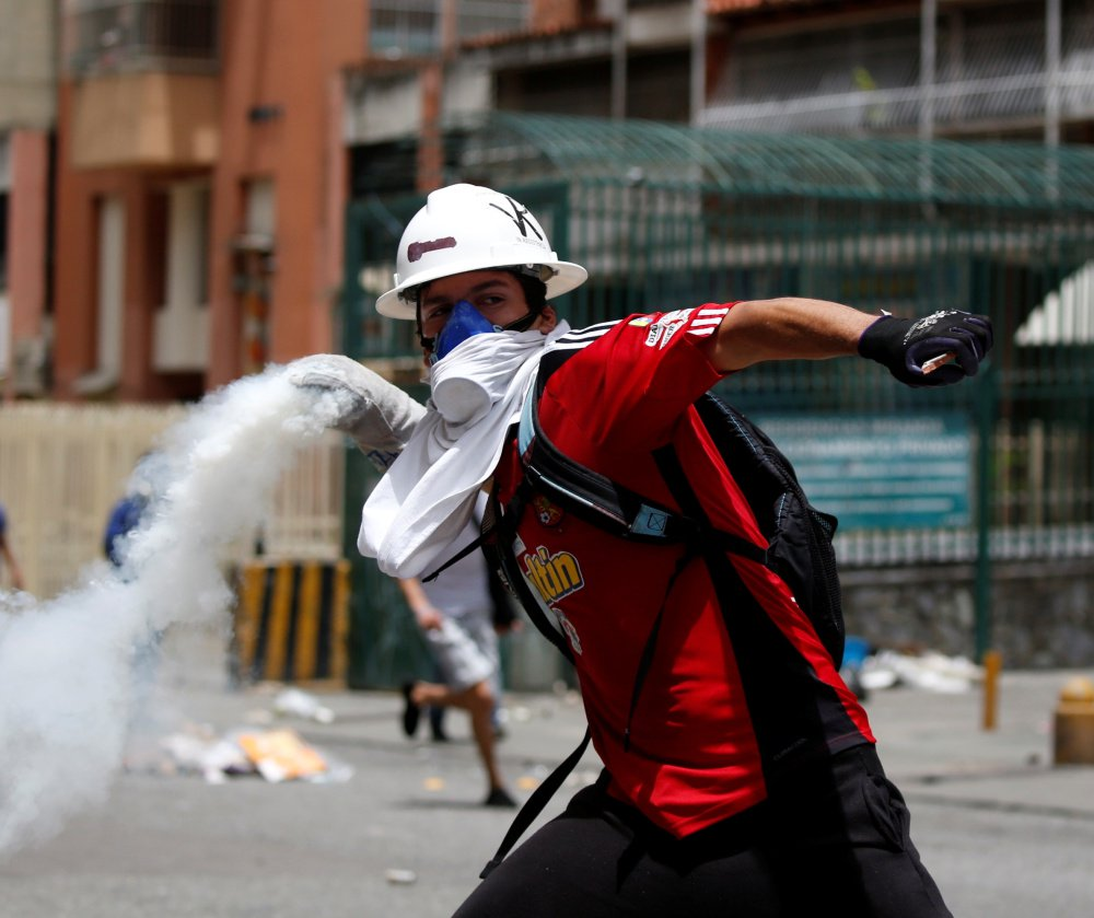 Demonstrators in Caracas clash with riot security forces while participating in a strike called to protest against Venezuelan President Nicolas Maduro.