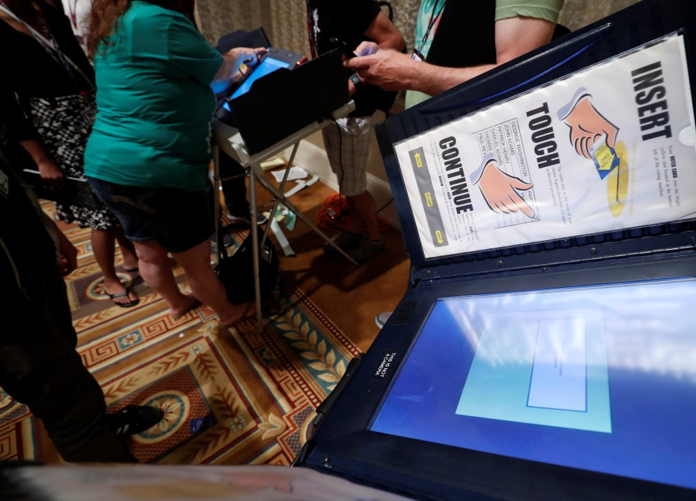 Hackers look over voting machines in a Voting Machine Hacking Village during the Def Con hacker convention in Las Vegas last week. The annual display of hacking skills revealed that many of the machines offered little in the way of security.
