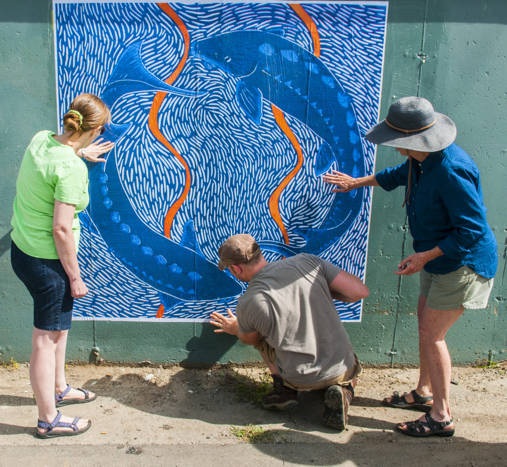 """From left, Barbara Whitten, Kerstin Gilg and Christine Olsen smooth out air bubbles after hanging a large-scale print Saturday on the bottom of Dennis' Pizza in the Arcade parking lot in Gardiner. The 6-by-6 foot print is of a 12-by-12-inch reduction linocut titled """"Endangered Shortnose Sturgeon,"""" done by Olsen. It was the first of several new large-scale paper prints to be attached to several walls with wheat paste that day. The event was a preview of the next Artwalk Gardiner, which is scheduled for 5:30 to 8 p.m. Friday in downtown Gardiner."""