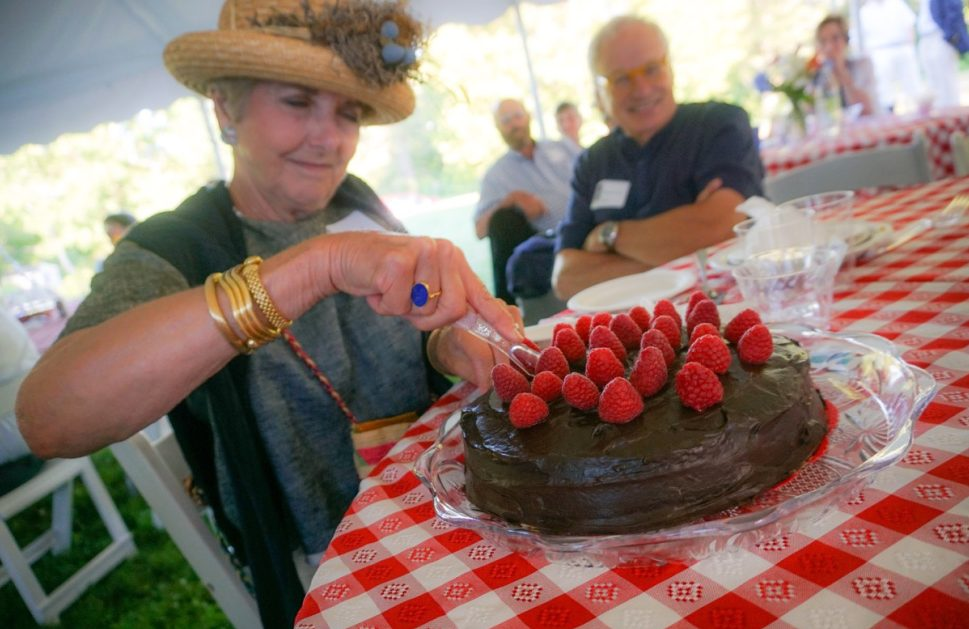 Luana Frois, of Westport Island, slices into a chocolate whiskey cake for which she and her husband were high bidders at Lincoln County Historical Association's Kermess at Pownalborough Court House.