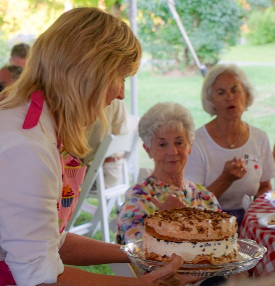 Terri Wells, of Wiscasset, displays Connie's Favorite Birthday Cake to guests at Lincoln County Historical Association's Kermess at Pownalborough Court House. Linda Belmont considers making a bid.