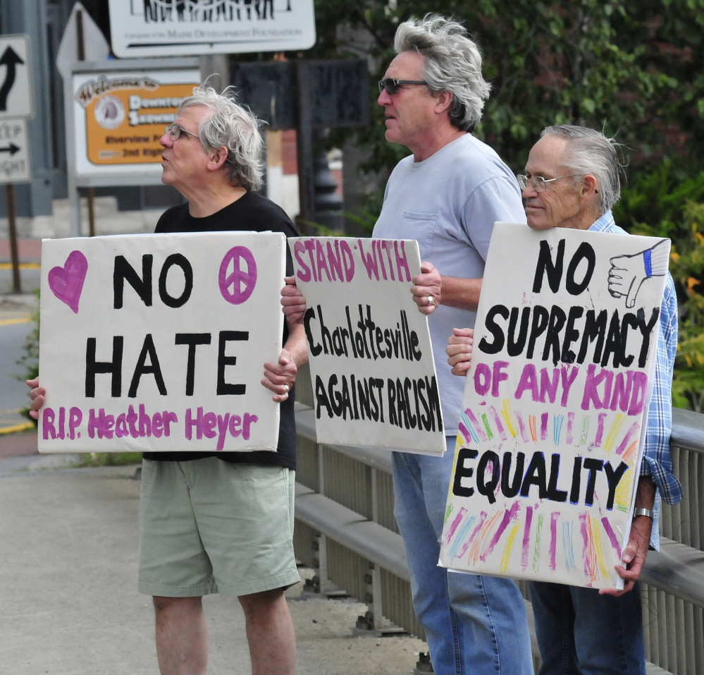 Protesters with Stand with Charlottesville Against White Supremacy hold signs against racism Sunday as motorists pass by in Skowhegan. From left are Mark Roman, Greg Williams and Dale Riddle.