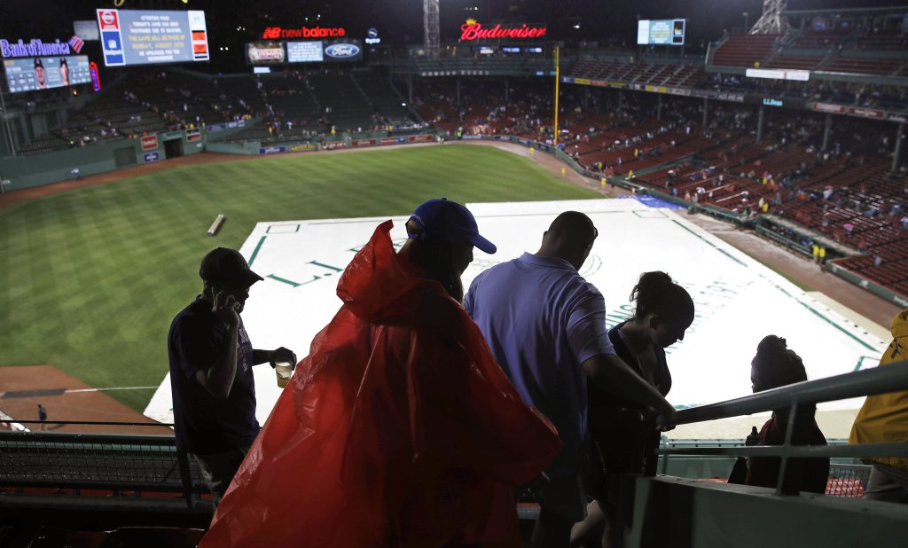 Fans leave Fenway Park after Wednesday's game between the Red Sox and Cleveland Indians was postponed due to heavy rain and thunderstorms.
