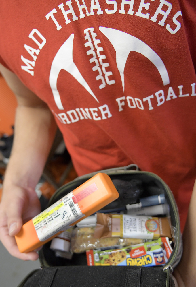 Staff photo by Andy Molloy   Gardiner safety Kolton Brochu checks the pack of supplies he carries to manage diabetes before practice Tuesday. The diabetic captain of the team checks his blood several times during practices and games and carries emergencies supplies, including Insulin.