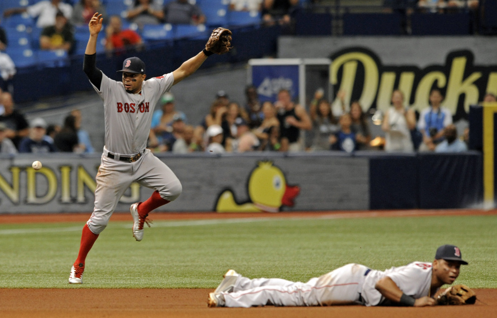 Boston shortstop Xander Bogaerts, left, and Rafael Devers cannot stop a ground ball single hit by Tampa Bay's Evan Longoria that drove in Jesus Sucre from third base during the fifth inning Sunda in St. Petersburg, Florida.