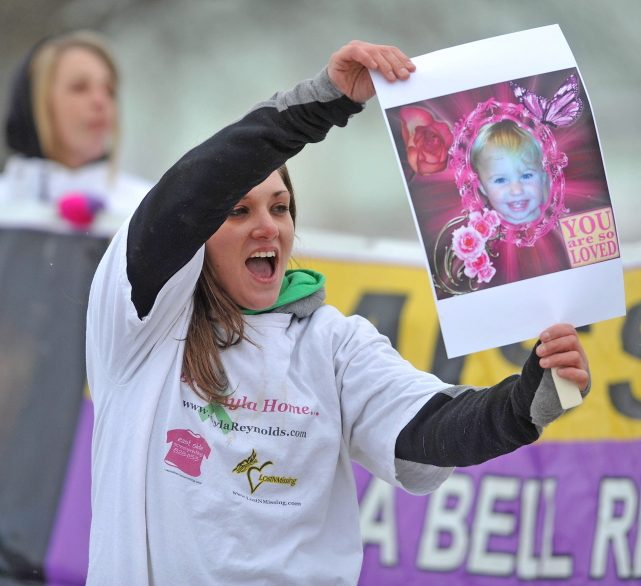 Trista Reynolds, mother of missing toddler Ayla Reynolds, holds a picture of her daughter in January 2014 at the Colby Circle and College Avenue intersection in Waterville during a rally. Trista Reynolds is seeking a formal court declaration that Ayla is dead so a wrongful death lawsuit can be pursued against Ayla's father, Justin DiPietro.