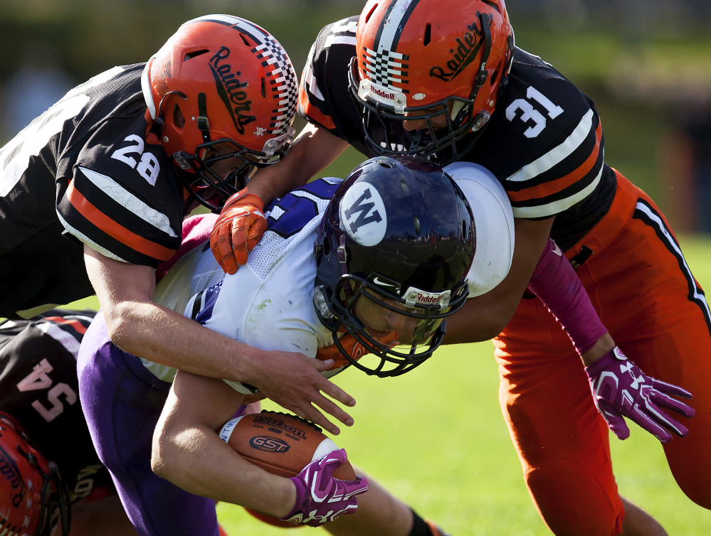 Winslow defenders Isaiah Goldsmith, left,  and Tyler Crayton bring down Waterville's Nicholas Wildhaber during a Class C North quarterfinal game Saturday at Poulin Field in Winslow.