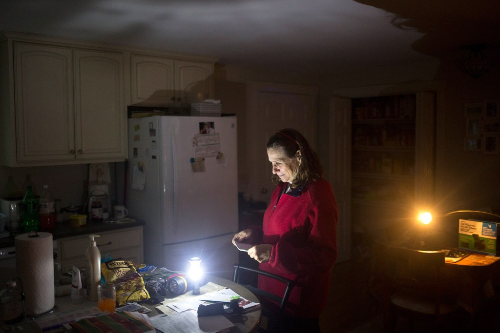 "Brenda Sherwin stands in her kitchen in Cumberland at dusk Thursday, illuminated by battery-powered lanterns. She and her husband haven't had power since early Monday morning. Four days isn't the longest they have been out of power. The couple had no power for 10 days after the ice storm in 1998. Sherwin, who does day care in her home, said, ""The worst part is not having coffee."""