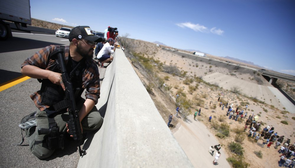 A Bundy supporter stands watch on a bridge in 2014 during a standoff between the Bundy family, their militia allies and the Bureau of Land Management near Bunkerville, Nev.
